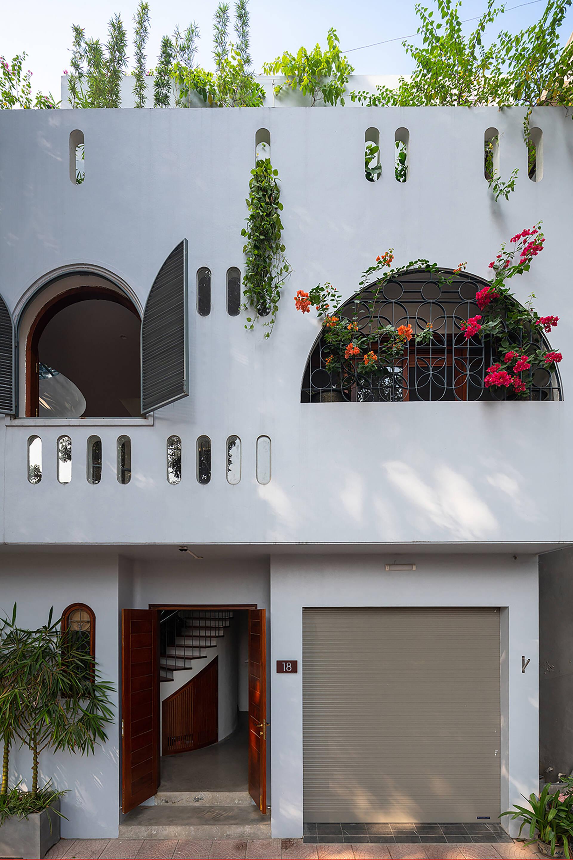 Cây rủ và hoa được trồng đan xen, vươn ra ngoài, mang lại cảnh quan tươi mới, đầy màu sắc cho L House