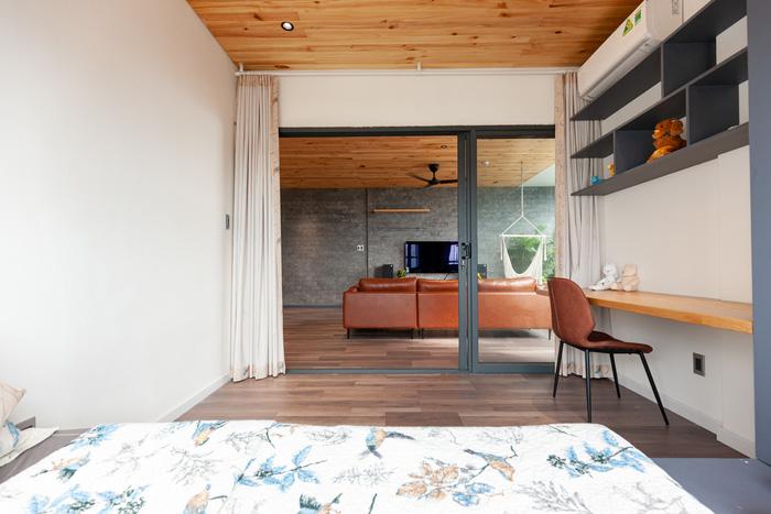 Phòng ngủ của con nhìn ra phòng khách, ngăn cách bằng tấm kiếng và màn cửa