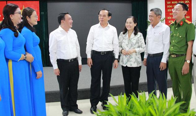 Bí thư Trung ương Ðảng, Bí thư Thành ủy TP HCM Nguyễn Văn Nên (giữa) và Chủ tịch HÐND TP Nguyễn Thị Lệ (thứ 3 từ phải sang) trao đổi với lãnh đạo quận 3