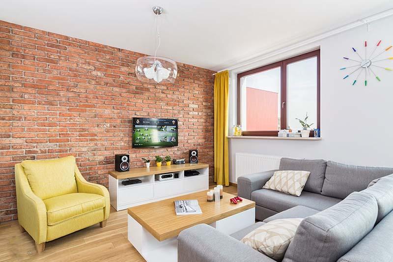 Trong phòng khách này, tường gạch nung đỏ không sơn trát giúp gia tăng chiều sâu cho căn phòng, đồng thời mang lại cảm giác thân thiện, chào đón