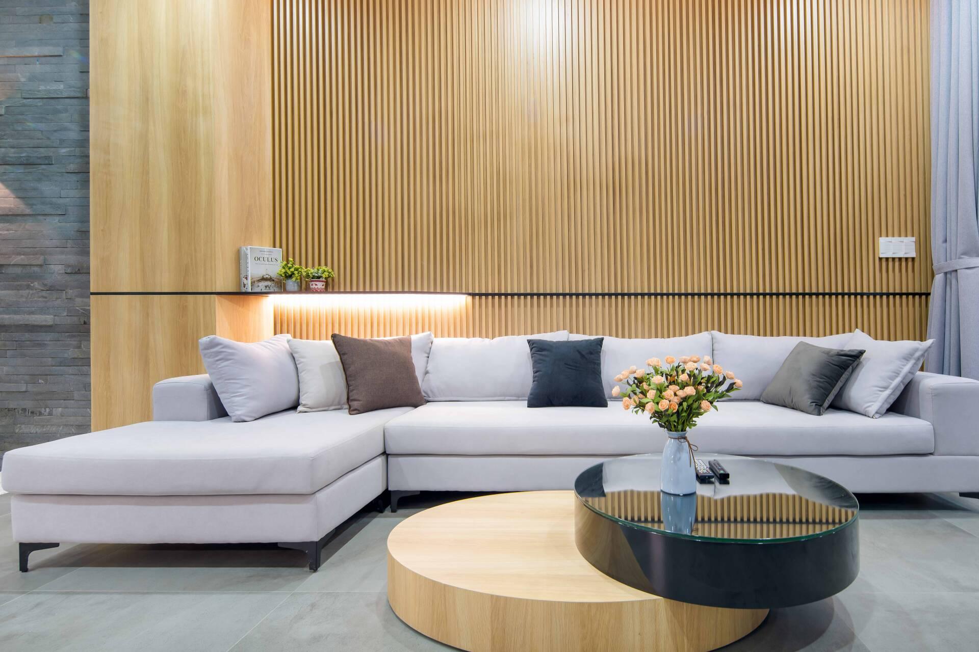 Để không gian có điểm nhấn, tường phía sau ghế sofa được ốp lam gỗ sáng màu