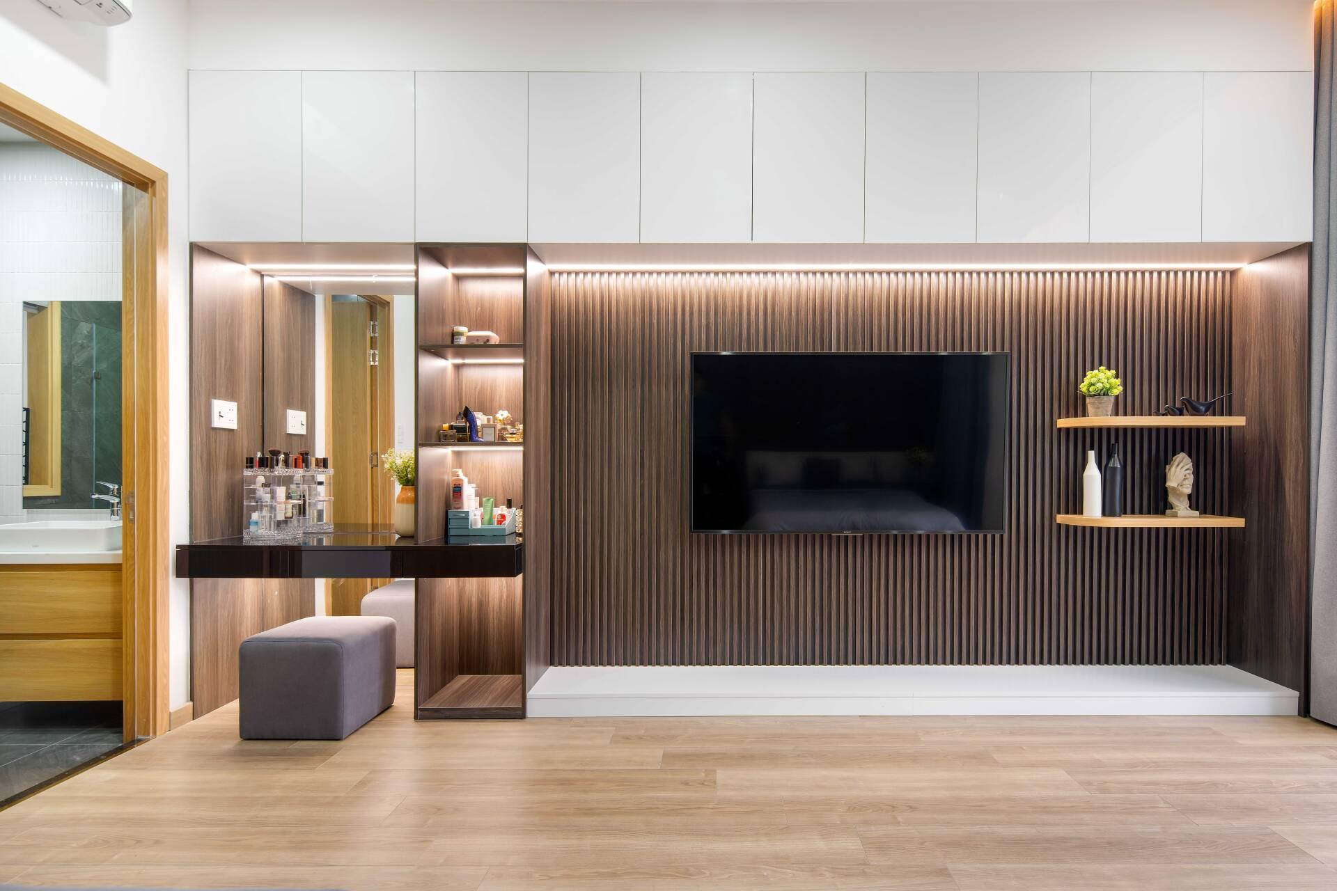 Tạo điểm nhấn cho không gian là bàn trang điểm và kệ tủ trang trí ở đối diện giường, KTS sử dụng gam màu gỗ nâu tối, thay vì là nâu sáng như tổng thể của phòng