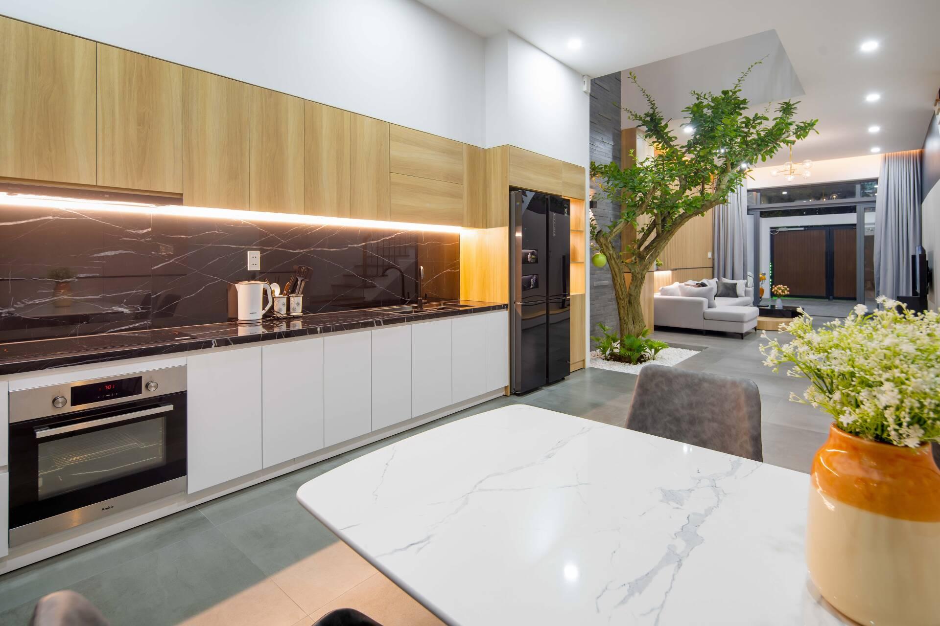 Hệ tủ bếp bằng gỗ MDF, phối cùng bàn bếp được ốp đá marble sang trọng