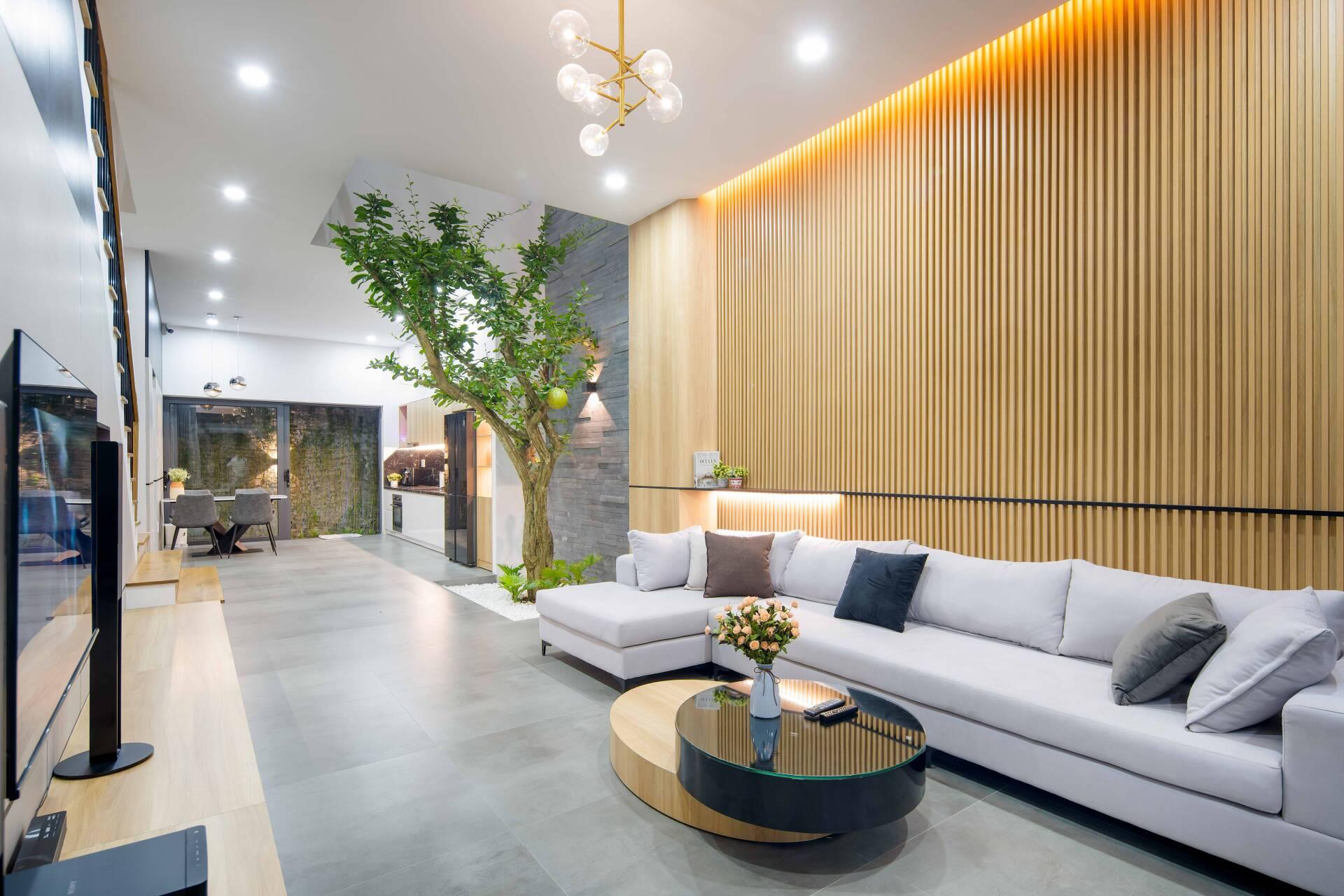 Sofa phòng khách mang gam màu xám sáng màu, phối cùng bàn trà hình tròn
