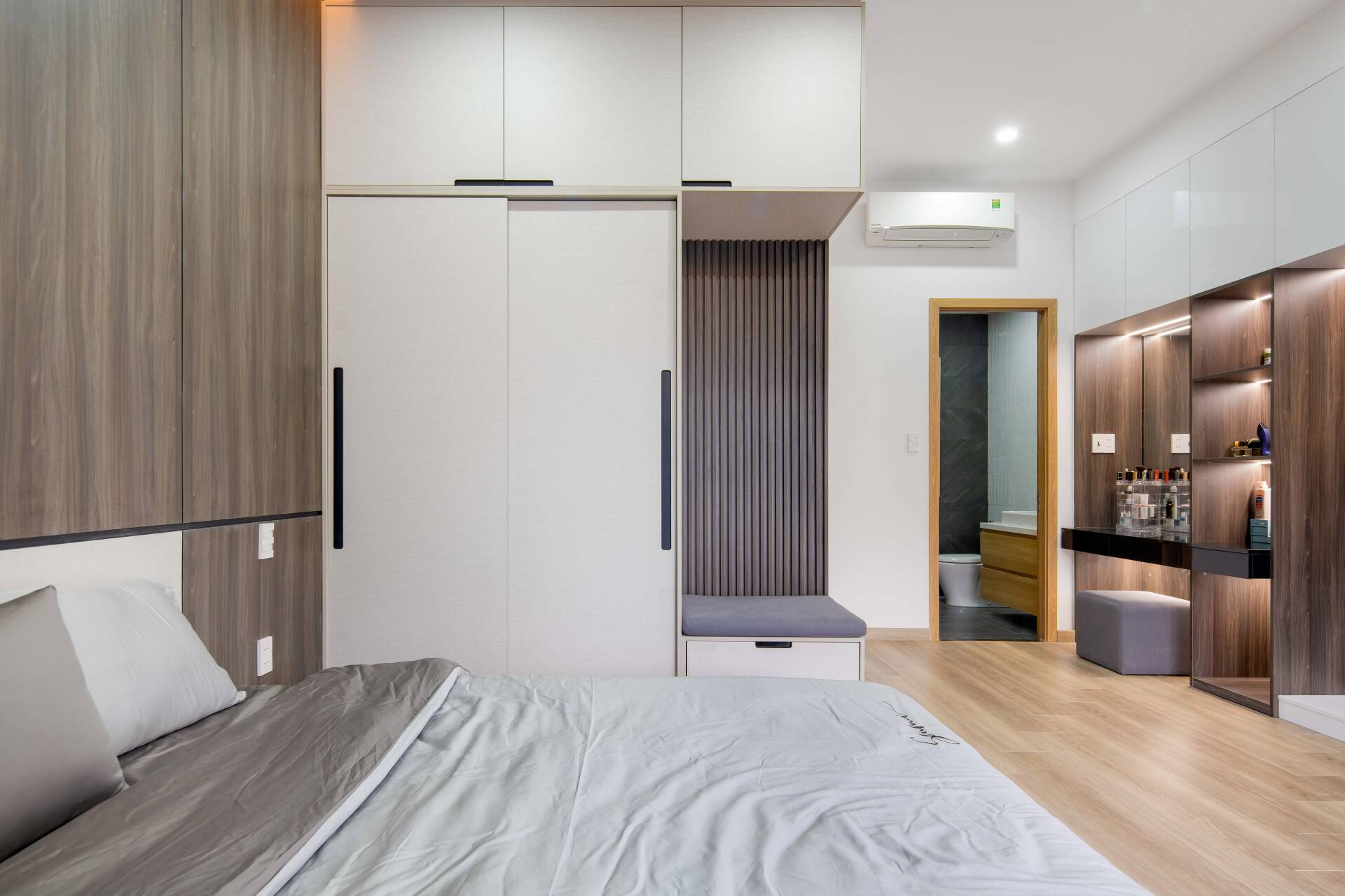 Để tiết kiệm không gian, hệ tủ quần áo được đóng chạm trần. Bên cạnh đó, có một ghế ngồi nhỏ ở cạnh tủ quần áo rất tiện nghi.