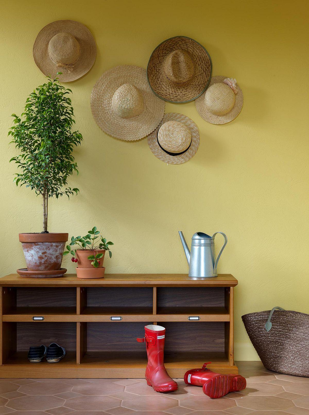Bức tường tạo điểm nhấn màu vàng êm dịu cho không gian nhập cảnh đương đại với giày và mũ