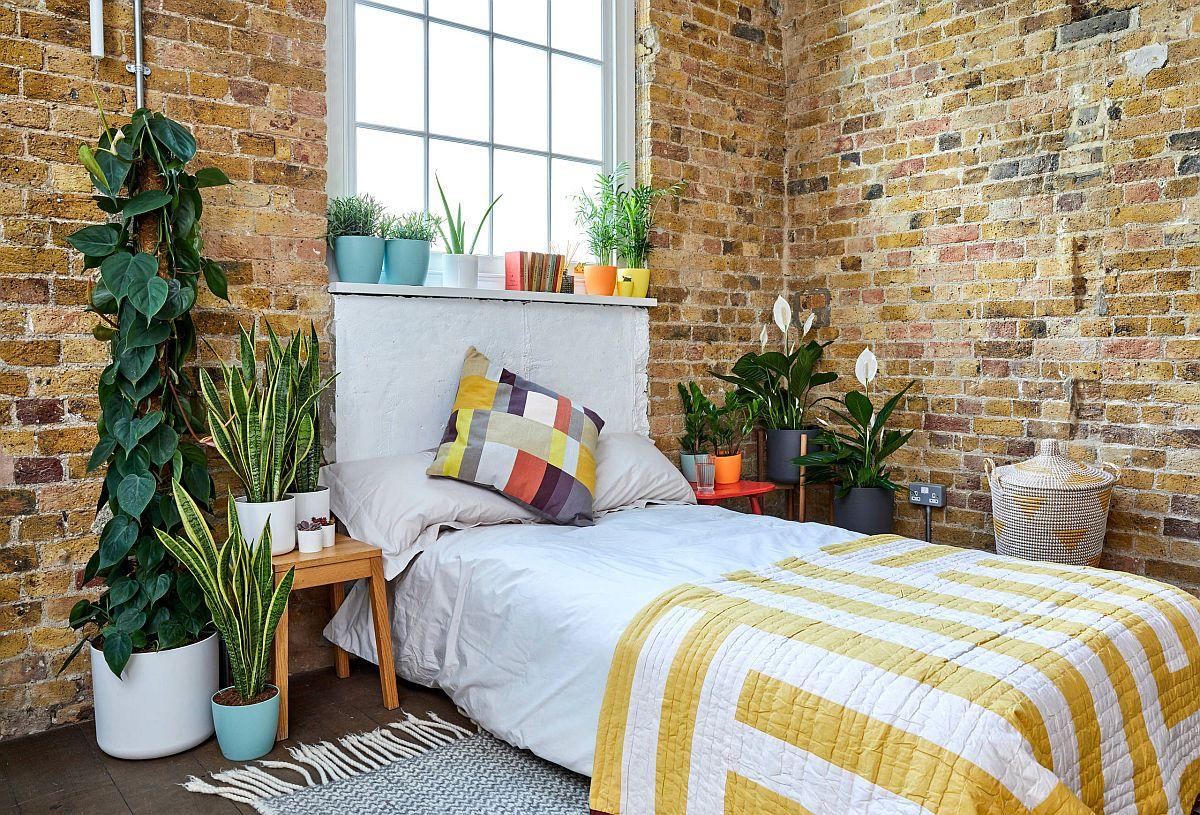Phòng ngủ công nghiệp hiện đại với tường gạch và cây xanh xung quanh