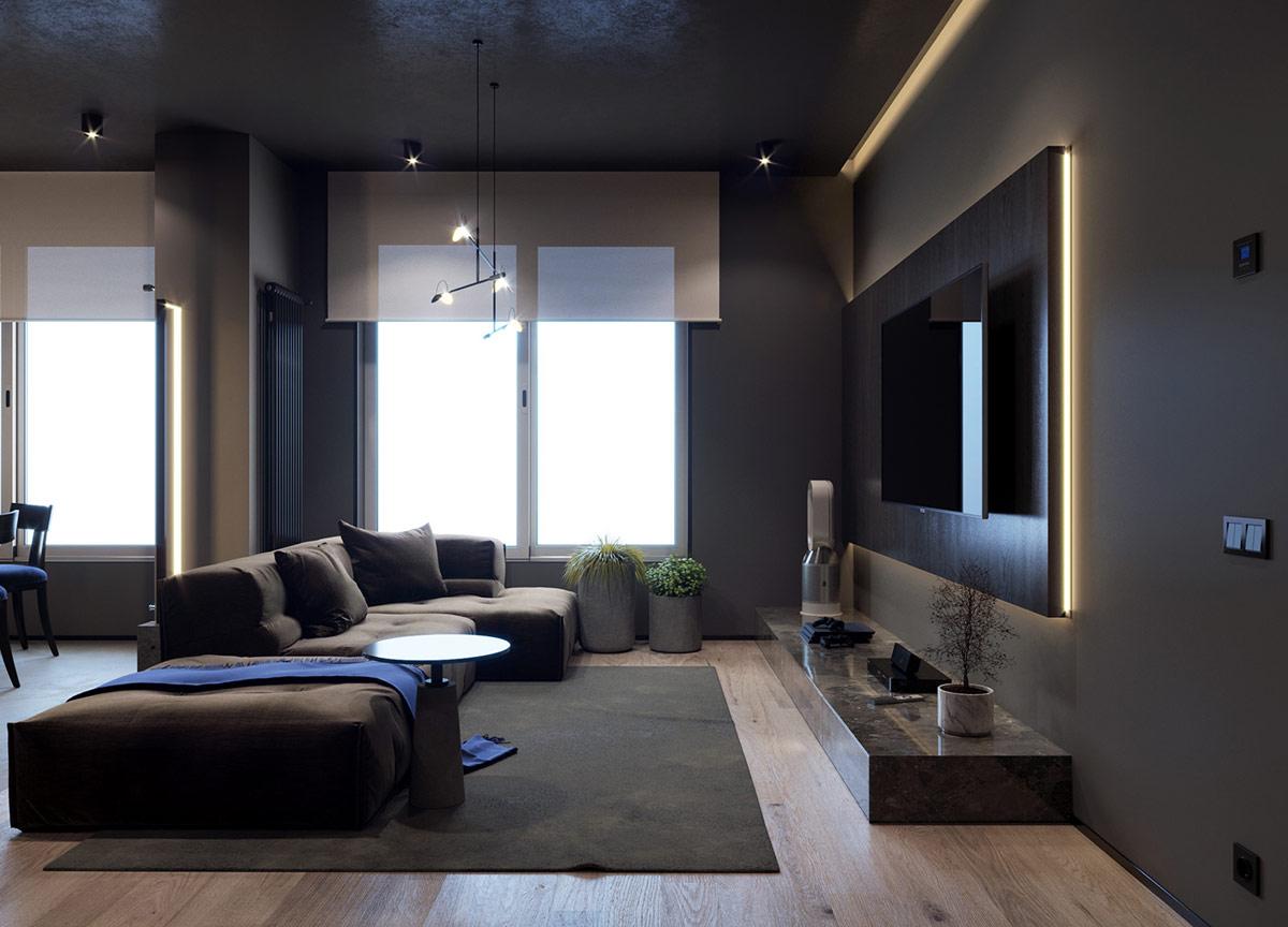 Cây trong nhà nép mình dưới cửa sổ, thu hút ánh nhìn xung quanh từ ghế sofa và lên bức tường TV được chiếu sáng