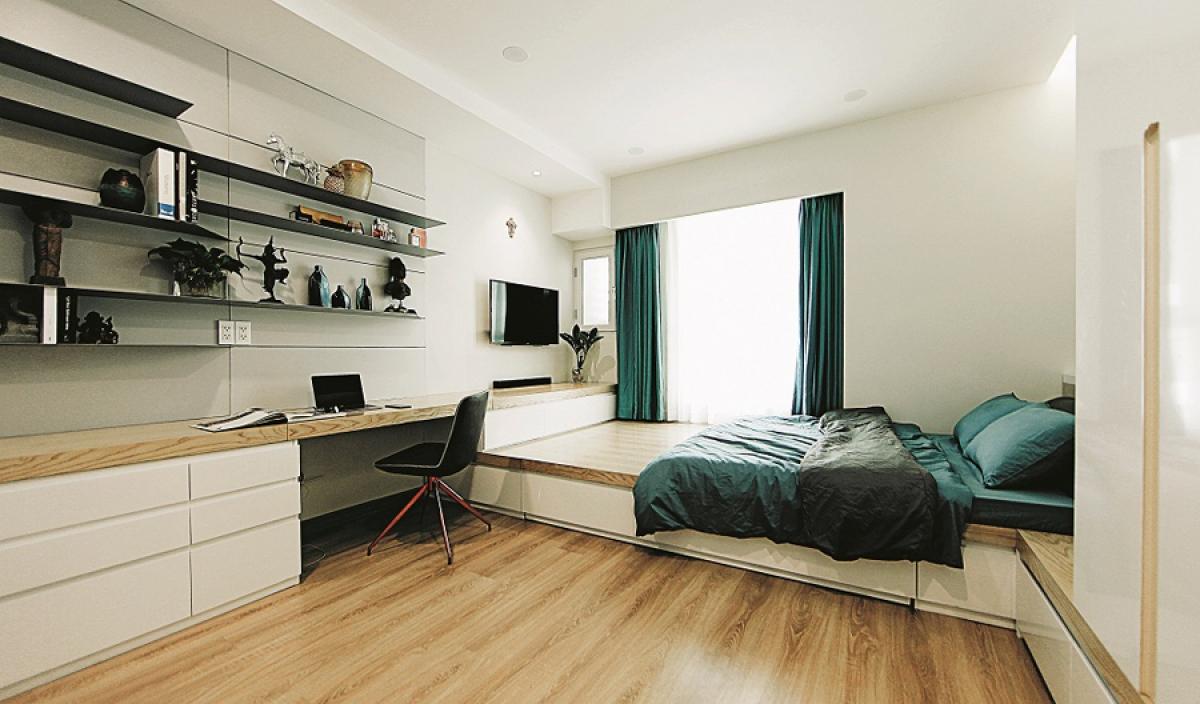 Cuối giường là kệ tivi liền kề với bàn làm việc. Hệ giá trên bàn được làm bằng thép mỏng cho cảm giác nhẹ nhàng. Giường, bàn… được tận dụng tối đa làm nơi chứa đồ theo kiểu nội thất thông minh.