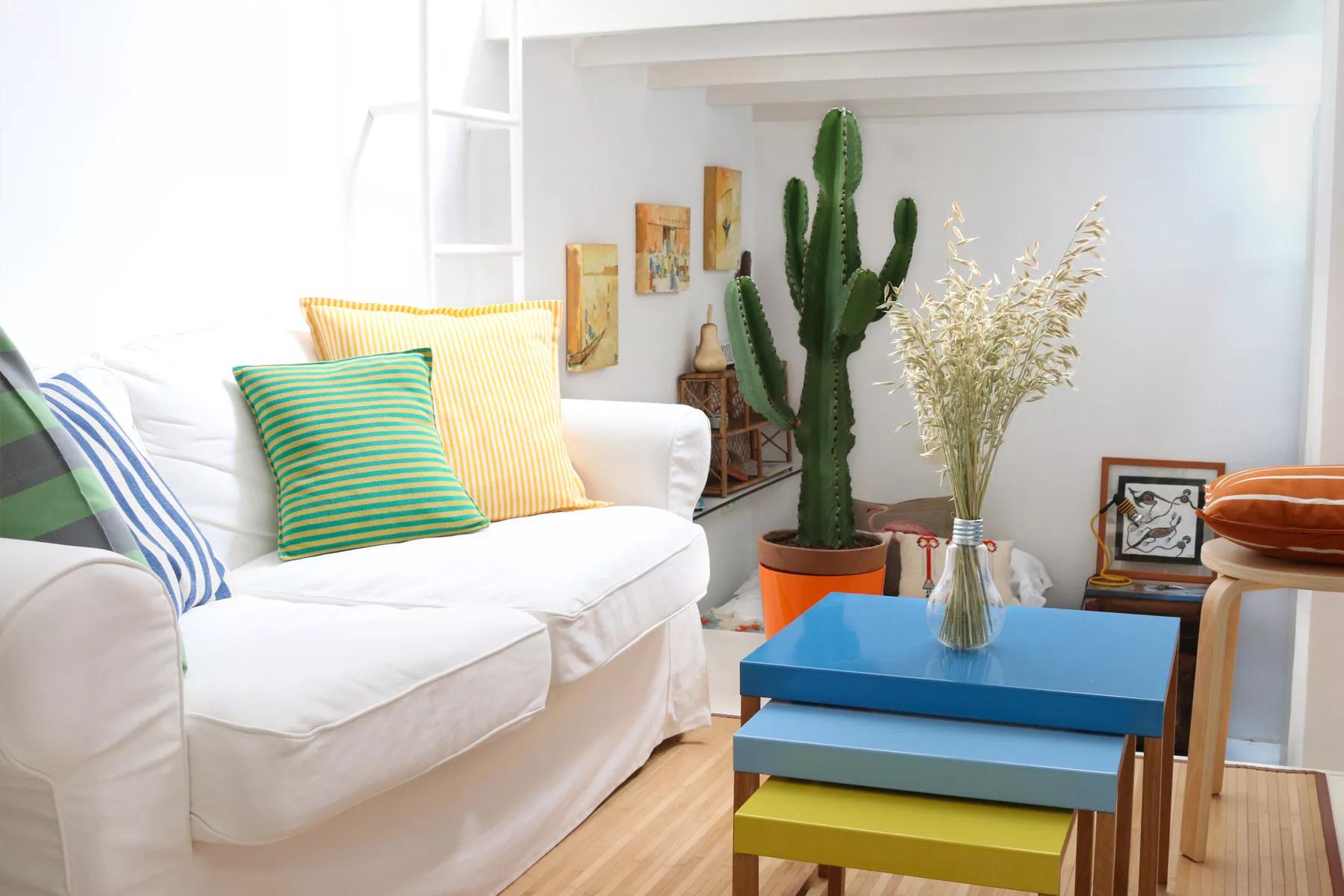 Những chiếc bàn bên lồng đầy màu sắc hoạt động như một bàn cà phê mở rộng. Một chiếc ghế đẩu bằng gỗ uốn cong nhỏ của IKEA có thêm một chỗ ngồi.