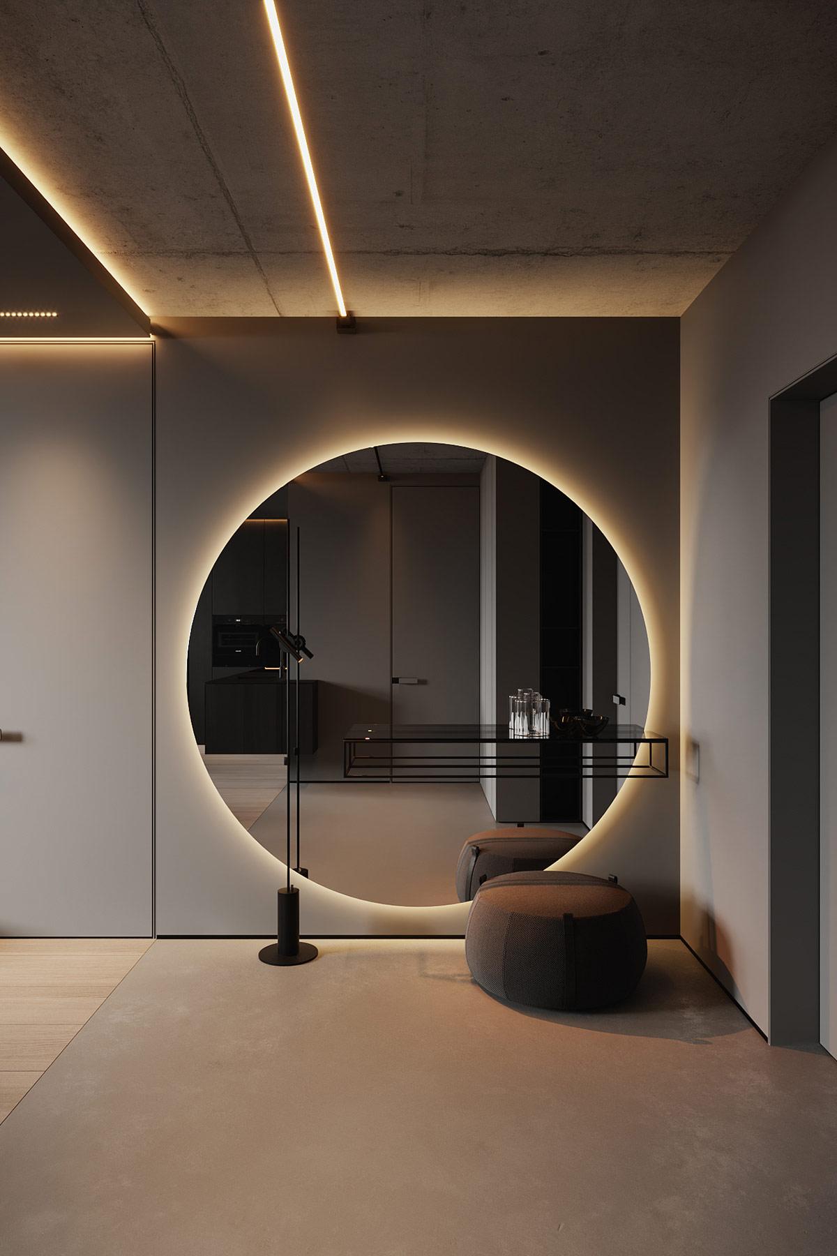 Một tấm gương treo tường trang trí lớn chiếu một vòng ánh sáng vào lối vào