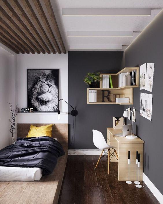 Căn phòng được decor khá nổi bật, bức tranh kết hợp với đèn ngủ treo tường ngay phía đầu giường, giường thiết kế dạng bệt khối gỗ, ga giường màu tối mang lại sự phức hợp nổi bật cho không gian nhỏ. Đối lập với nó là bàn học và kệ gỗ treo tường màu nâu gỗ vàng sáng, thiết ké tận dụng cắt góc giúp cân bằng những khoảng trống.