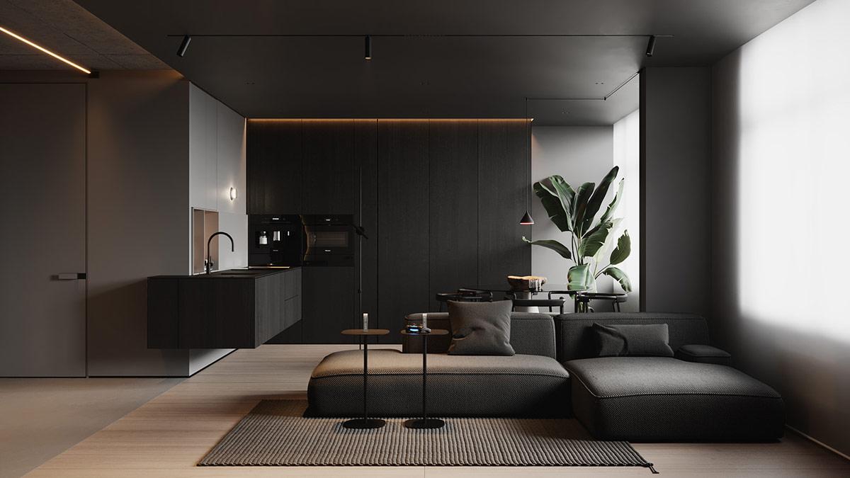 Một chiếc ghế sofa hiện đại có đường nét thấp trượt một hình bóng tuyến tính trên tấm thảm than hoa văn trong phòng khách, trong khi nhà bếp màu đen được nâng lên đường mái được chiếu sáng phía sau.