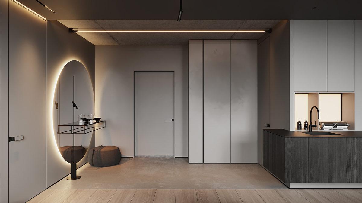 Một thiết bị chiếu sáng tuyến tính phía trên một lối vào nhà bằng bê tông. Tủ quần áo màu xám ở hành lang kết hợp liền mạch với nhau thành một thiết kế nhà bếp màu xám