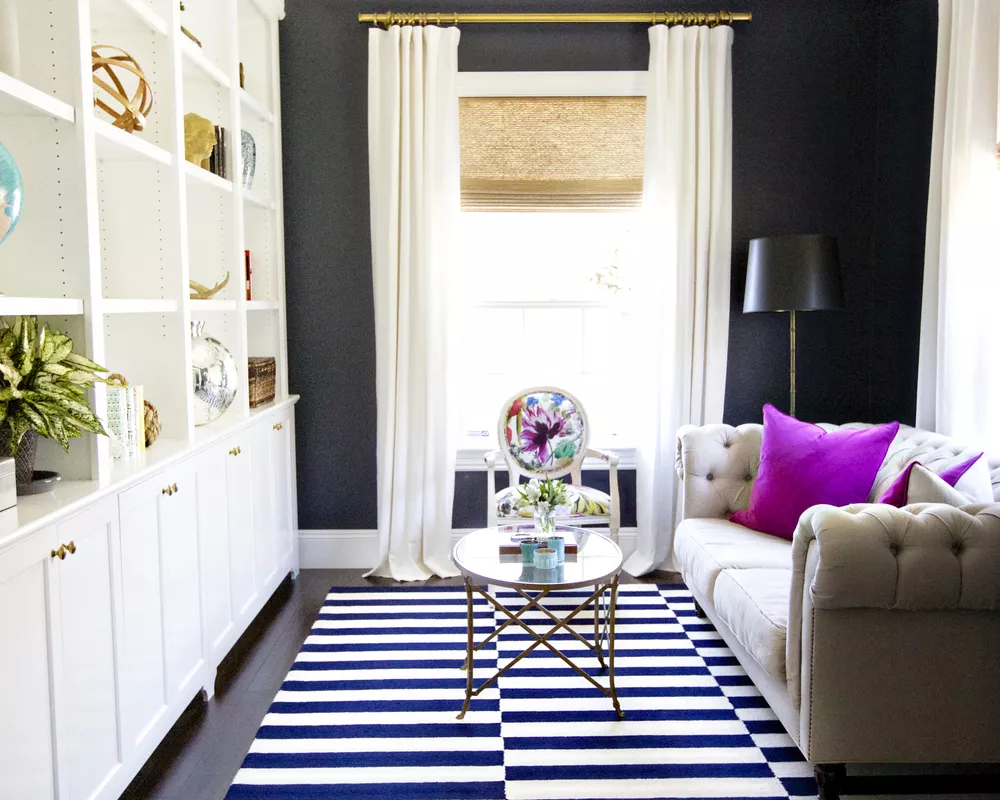 Những bức tường đen tạo thêm chiều sâu cho phòng khách nhỏ này của công ty thiết kế nội thất Studio McGee có trụ sở tại Utah . Nhiều ánh sáng mặt trời và bộ lưu trữ màu trắng cao ở bên trái giúp không gian không có cảm giác chật chội hoặc buồn tẻ. Một tấm thảm sọc rẻ tiền giúp giữ vững căn phòng. Chiếc ghế sofa sang trọng làm cho mọi thứ trở nên hấp dẫn hơn. Chiếc ghế bành tạo thêm sự thích thú đầy màu sắc. Chiếc bàn cà phê mặt kính hình bầu dục chiếm rất ít không gian thị giác.