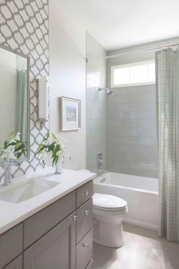 Bức tường có giấy dán tường với hoa văn phía sau gương chính là điểm nhấn cho phòng tắm nhỏ này trông đẹp hơn