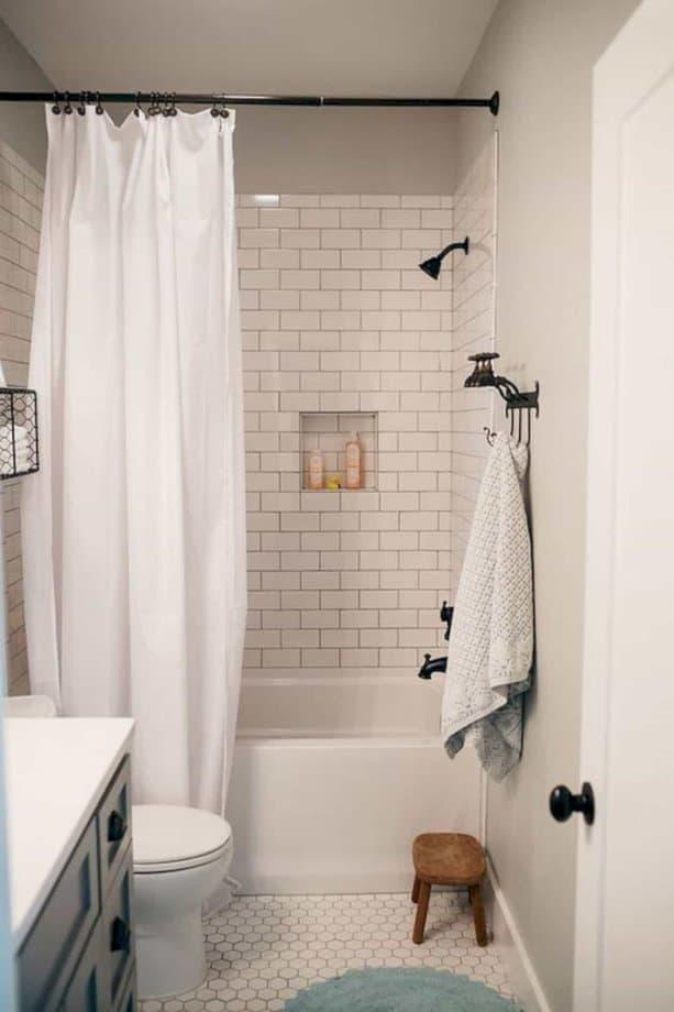 Điều làm phòng tắm nhỏ này trông đáng yêu là chiếc rèm màu trắng và gạch lát nền mosaic