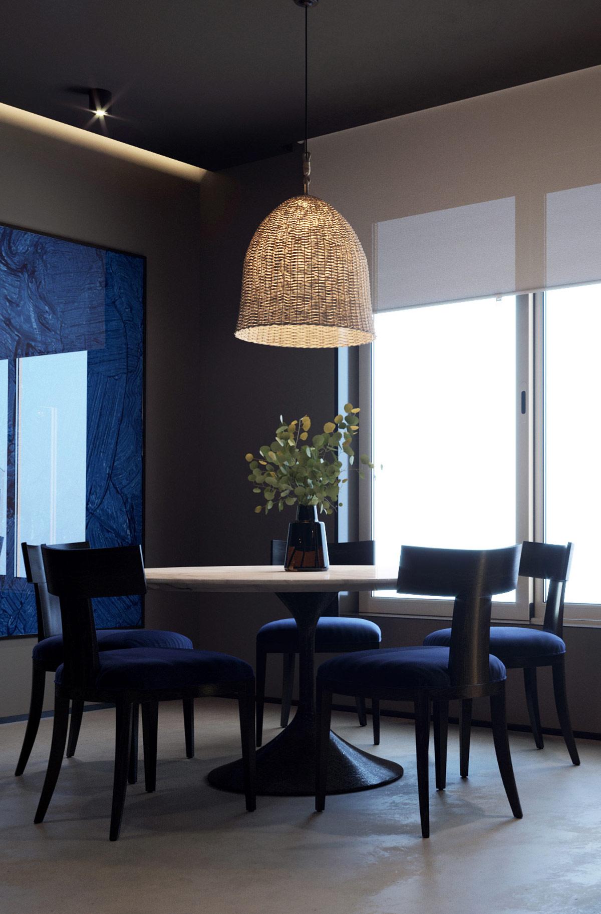 chiếu sáng xuống bàn ăn có bệ tròn  bằng đá cẩm thạch bóng loáng . Bóng râm tự nhiên tạo nên sự tương phản tinh tế về màu sắc với môi trường xung quanh được trang trí tối và những chiếc ghế ăn bọc đệm màu xanh sang trọng. Nghệ thuật treo tường hiện đại làm tràn điểm nhấn màu xanh lam lên bức tường phòng ăn màu xám đầy buồn bã.
