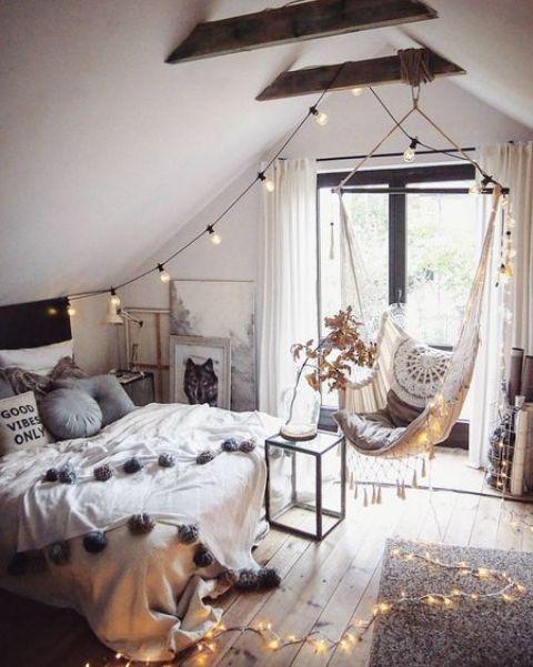 một căn phòng áp mái kiểu boho dành cho thanh thiếu niên với giường, ghế lơ lửng, đèn chiếu sáng và rất nhiều tác phẩm nghệ thuật là một không gian đáng yêu