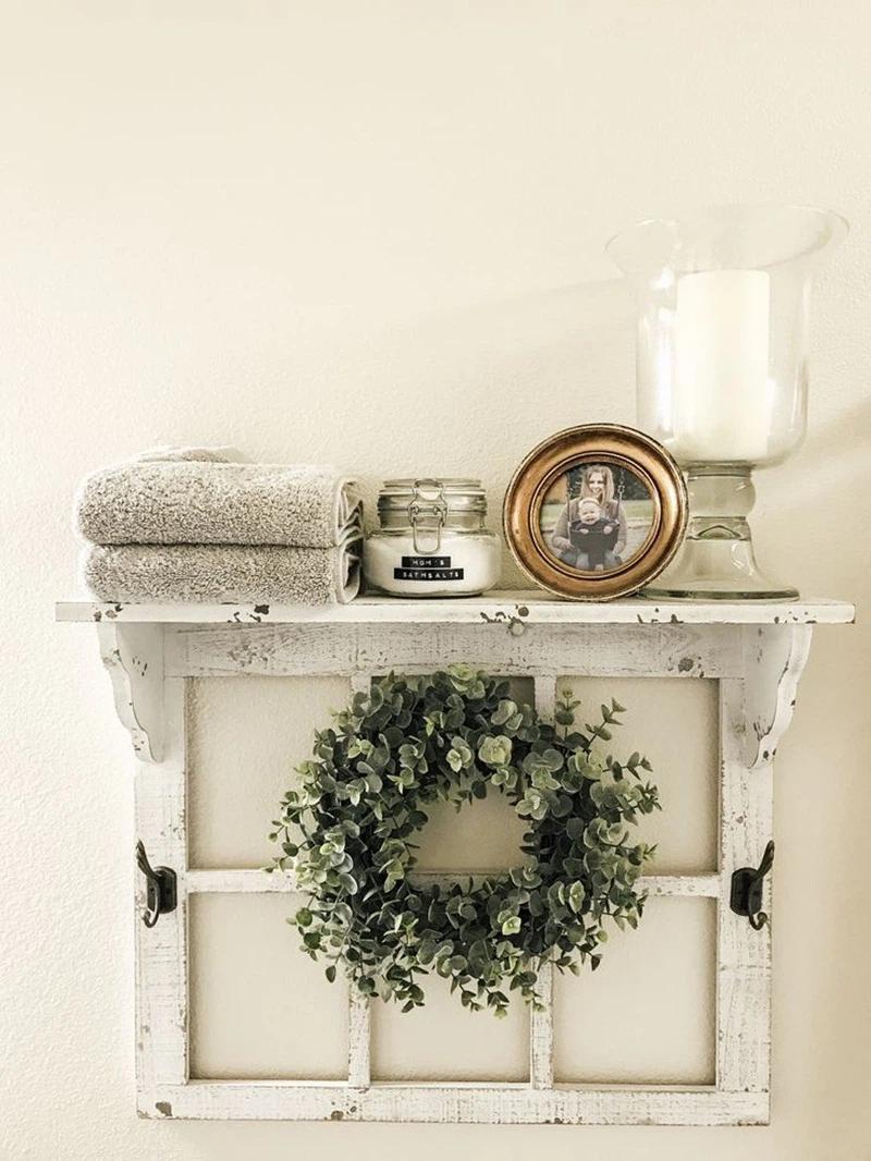 Một chiếc kệ từ khung cửa sổ cũ, với một vòng hoa được bện bằng cây xanh, một ngọn nến, một bức ảnh, và vài chiếc khăn là lý tưởng cho phòng tắm tinh tế.