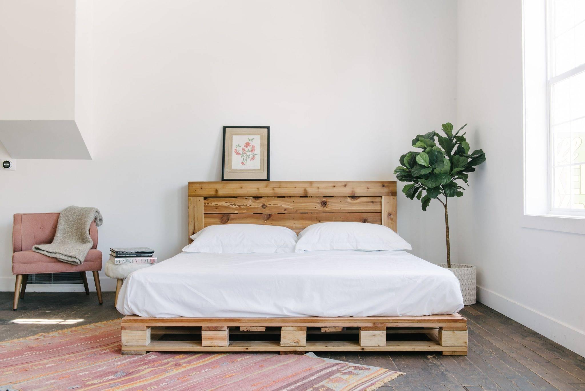 Phòng ngủ tối giản với giường pallet và ghế tạo điểm nhấn