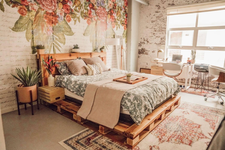 Phòng ngủ cực kỳ sang trọng này có giường pallet quét vôi trắng bên dưới chăn, thảm và tông màu hồng có họa tiết thơ mộng