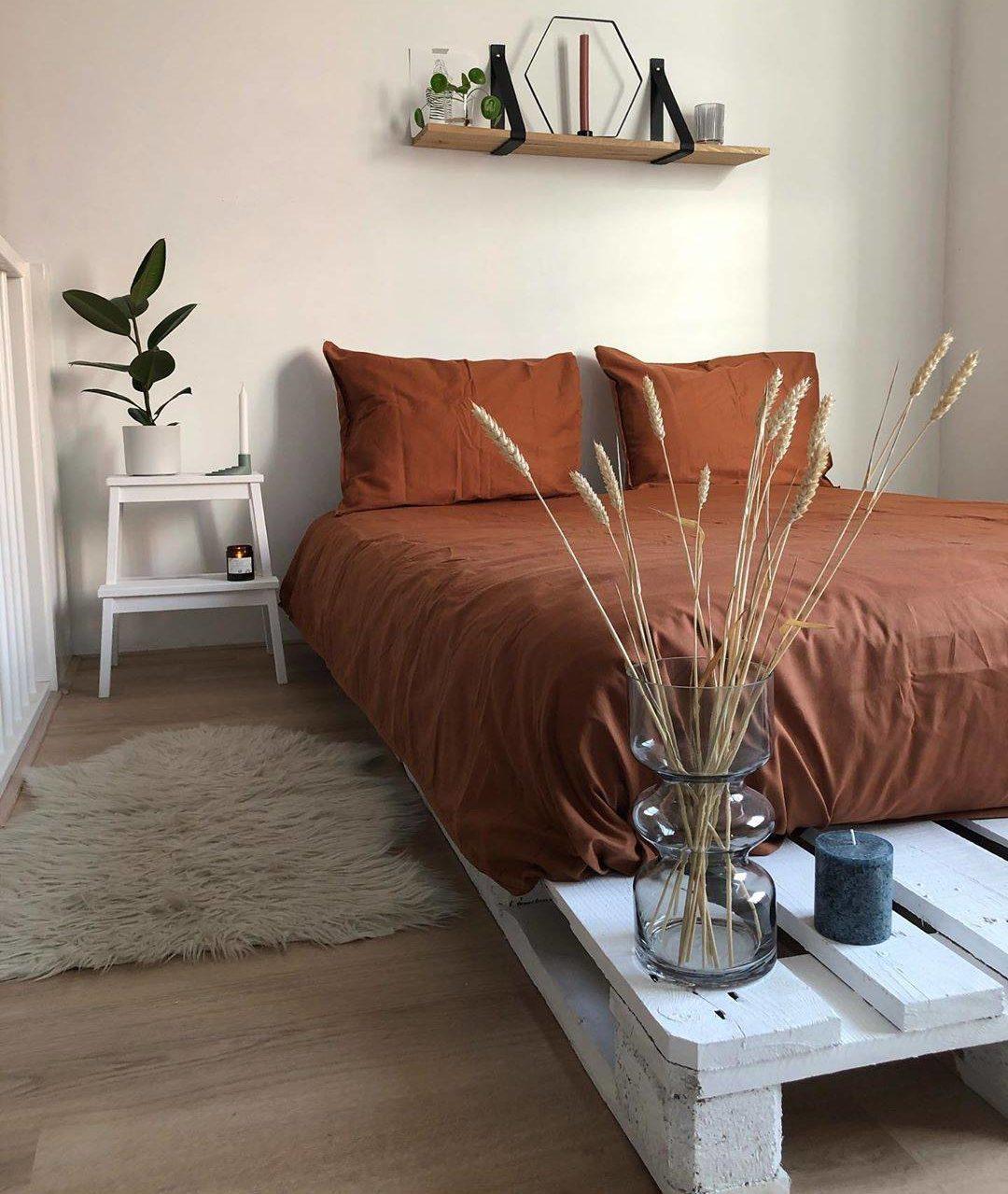 Một chiếc giường nền bằng ván pallet quét vôi trắng và bộ khăn trải giường tông màu đất nung hoàn thiện căn phòng tối giản tuyệt đẹp này