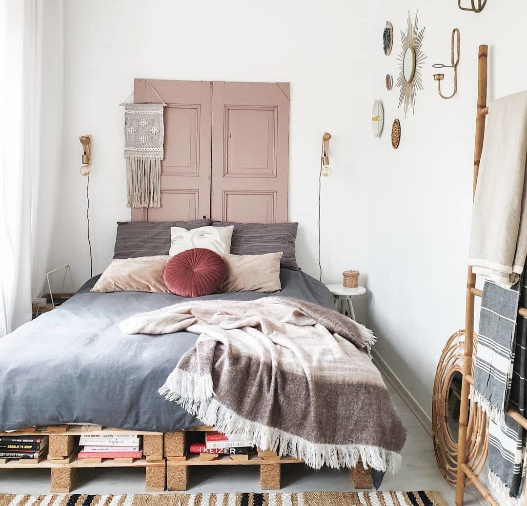 Các pallet xếp chồng đôi làm bằng ván dăm đóng vai trò vừa là nơi lưu trữ vừa là khung giường theo phong cách mộc mạc trong căn phòng boho đồng quê này