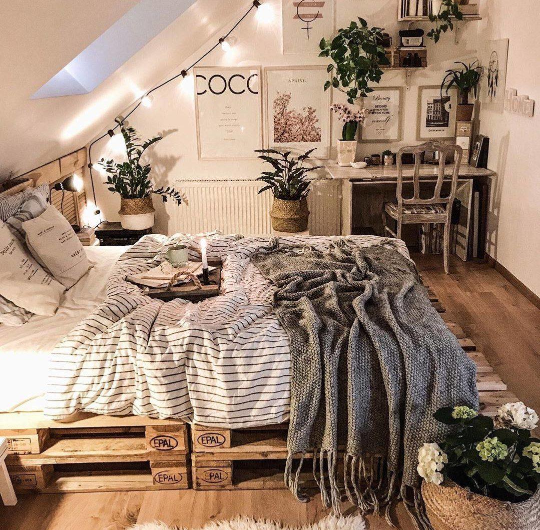 Phòng ngủ nông thôn mộc mạc ấm cúng có giường pallet đôi, ghế cổ và giỏ dây đay tự nhiên