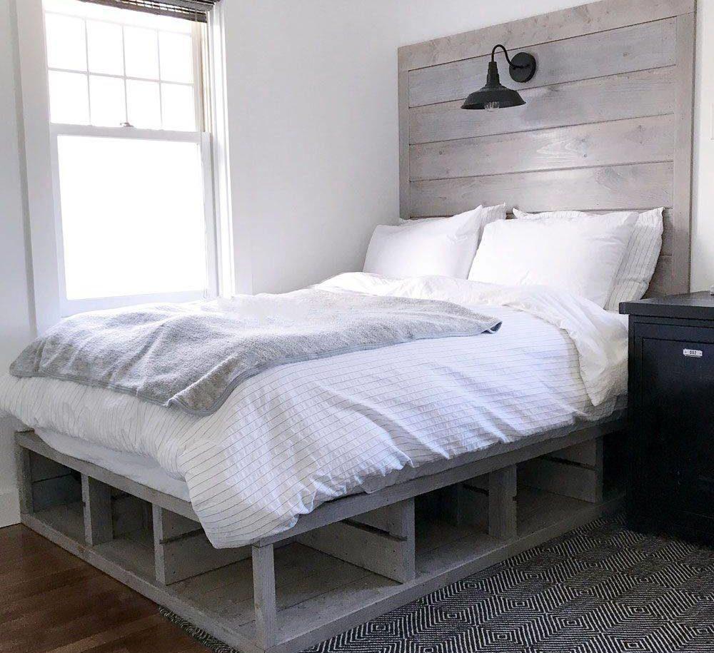 giường lấy cảm hứng từ pallet tùy chỉnh sạch sẽ này có các ngăn chứa đồ mở bên dưới và đầu giường màu xám mộc mạc với thiết bị chiếu sáng tích hợp