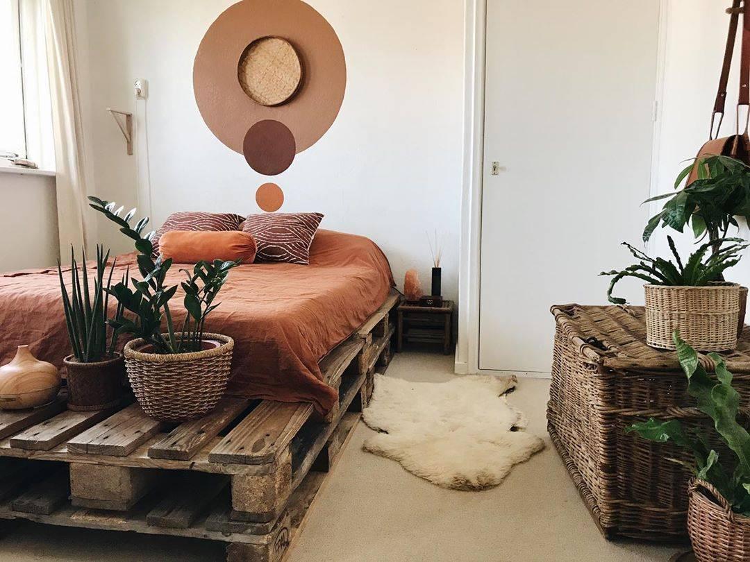 Tông màu đất Terra cotta và giỏ đan bằng liễu gai tôn lên chất gỗ tự nhiên mòn của khung giường pallet