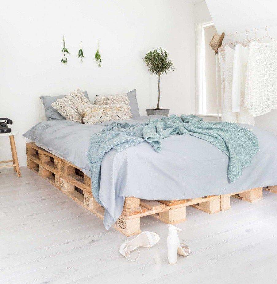 Một phòng ngủ sang trọng ven biển, sạch sẽ dựa trên nền tảng pallet gỗ mộc mạc làm khung giường và sử dụng bộ khăn trải giường bằng vải lanh màu xanh nhạt để hoàn thiện vẻ ngoài