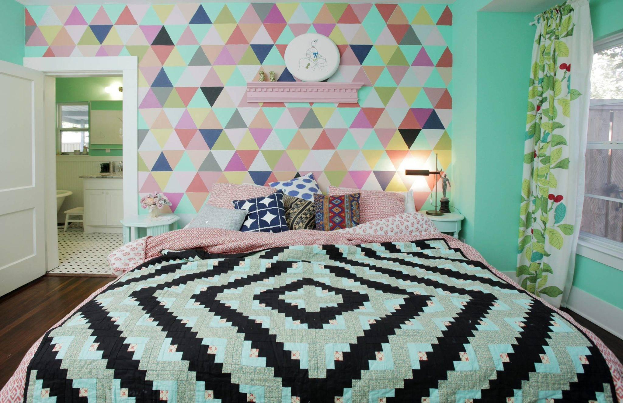 Một phòng ngủ màu xanh ngọc tươi sáng được tôn lên bởi bức tường có điểm nhấn địa lý được hoàn thiện bằng cách sử dụng giấy dán tường hoặc giấy dán tường. Các mẫu hỗn hợp trên bộ đồ giường chần bông và rèm cửa màu xanh lá cây hoàn thiện kế hoạch trang trí cho phòng ngủ sôi động này.