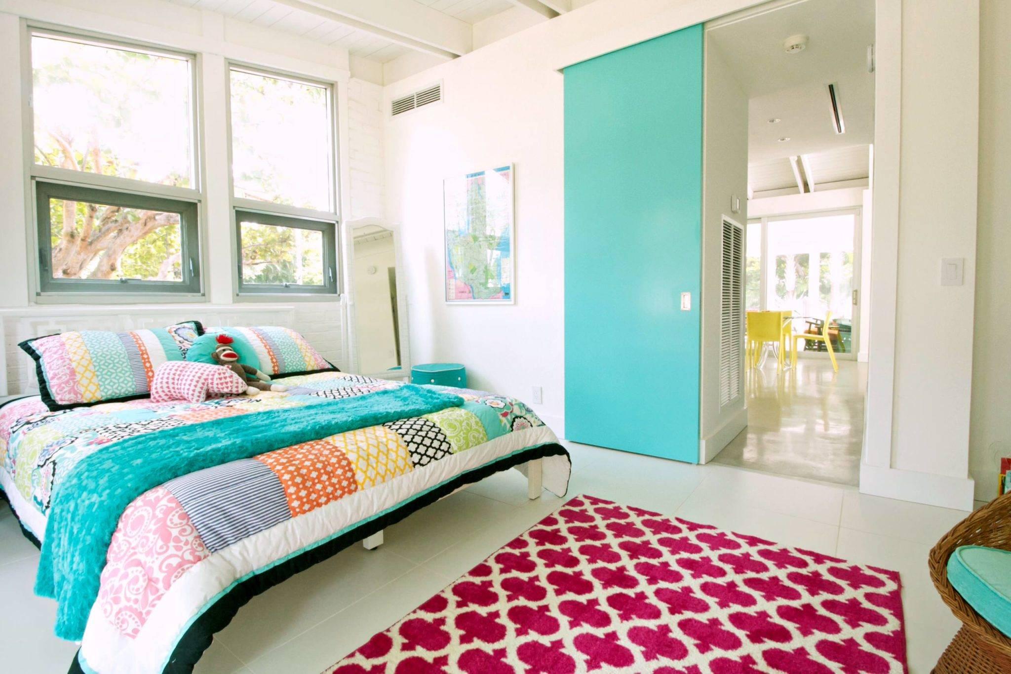 Phòng ngủ toàn màu trắng này được trang trí với màu xanh mòng két và xanh lam đậm để tạo cảm giác vui vẻ và tươi sáng cho căn phòng. Một chiếc chăn bông nhiều màu và một tấm thảm màu đỏ có hoa văn giữ cho căn phòng ấm cúng và hợp thời trang đồng thời.
