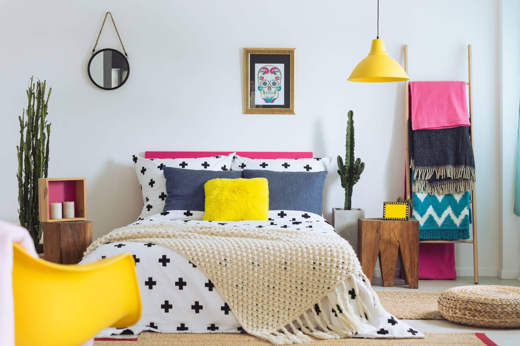 Trang trí màu vàng và hồng, bao gồm gối ném, đèn chiếu sáng và một chiếc ghế màu vàng, là những đặc điểm nổi bật của phòng ngủ màu trắng này. Bậc thang chăn với những chiếc chăn có hoa văn tươi sáng tạo nên sự thoải mái và giúp hoàn thiện bảng màu mùa hè.