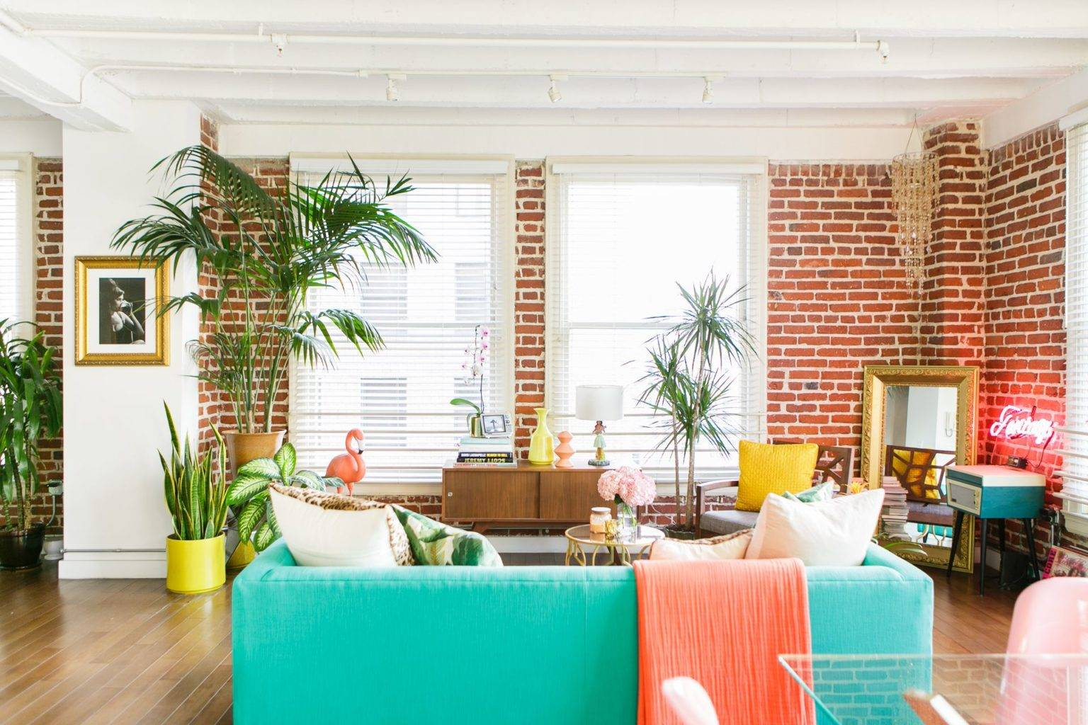 Căn hộ có nội thất bằng gạch đỏ được trang trí với tông màu vàng và san hô đậm bao quanh chiếc ghế sofa màu xanh ngọc làm trung tâm trong căn gác xép đầy màu sắc này.