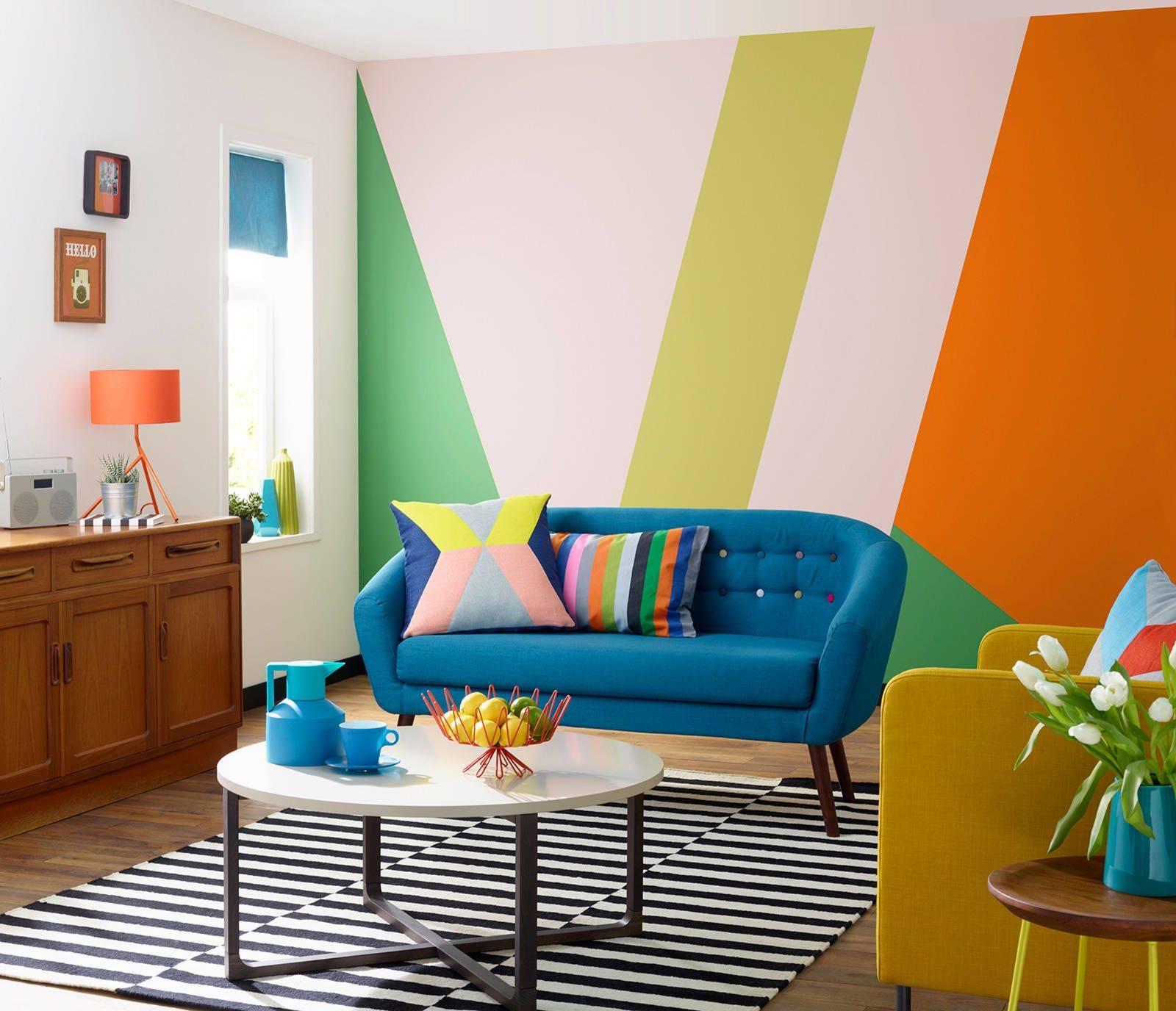 Phòng khách sôi động này có sự kết hợp của nhiều màu sắc tươi sáng trên một bức tường với điểm nhấn là các khối hình học ngẫu nhiên để thu hút sự chú ý vào không gian. Chiếc ghế dài màu xanh đậm và các chi tiết trang trí bổ sung như chậu hoa và chân bàn màu vàng giúp gắn kết không gian với nhau.