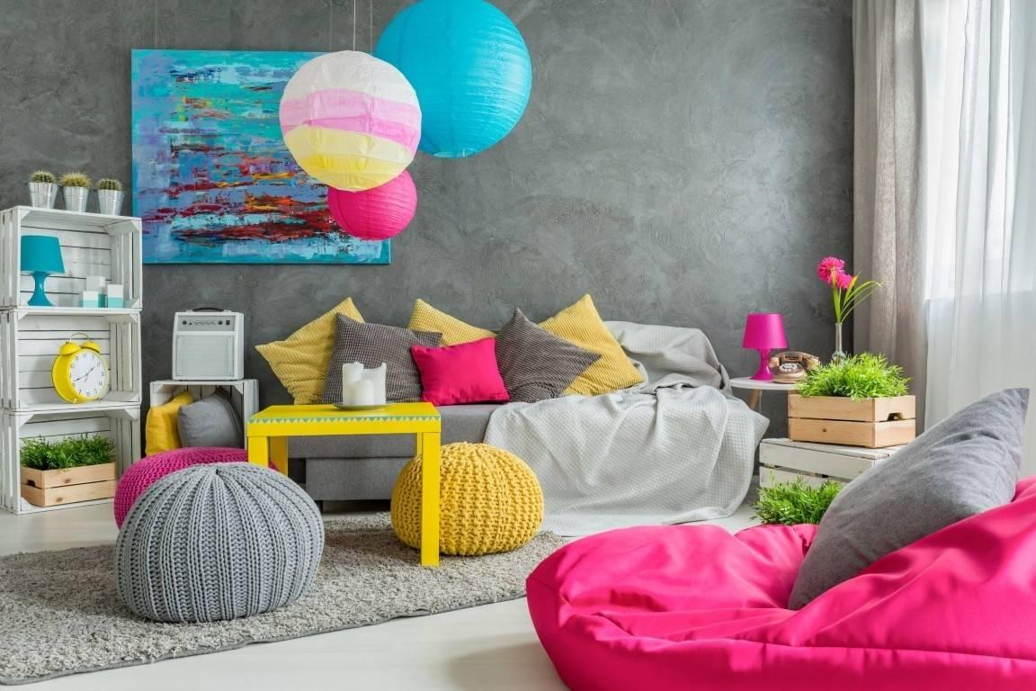 khách tông màu xám này trở nên thú vị hơn nhiều với việc bổ sung một chiếc ghế bọc hạt đậu lớn màu hồng, những chiếc gối màu vàng và hồng, và những chiếc khăn trải sàn nhiều màu. Các điểm nhấn màu xanh lam thêm các mảng màu tươi sáng nơi chúng được đặt xung quanh phòng và một chiếc bàn cà phê màu vàng tươi nằm ở trung tâm trong bảng màu vui nhộn này.
