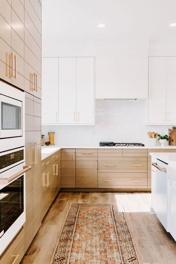 Tủ dưới màu sáng và tủ trên màu trắng cùng hệ thống hút mùi liền mạch và nền gạch bóng màu trắng