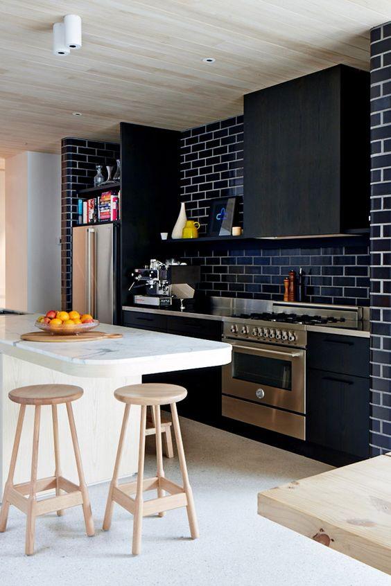 Nhà bếp màu đen hiện đại sang trọng với máy hút mùi phù hợp , tấm ốp lát gạch tàu điện ngầm màu xanh nước biển, mặt bàn bằng kim loại đầy phong cách và táo bạo