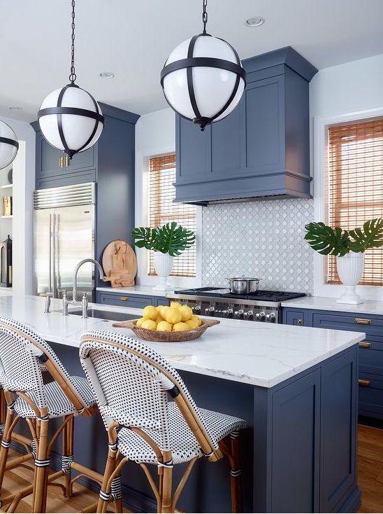 hà bếp nhiệt đới mát mẻ với tủ màu xanh lam và một chiếc bếp phù hợp, tấm lát nền bằng gạch, mặt bàn bằng đá trắng và những chiếc ghế đẩu bắt mắt
