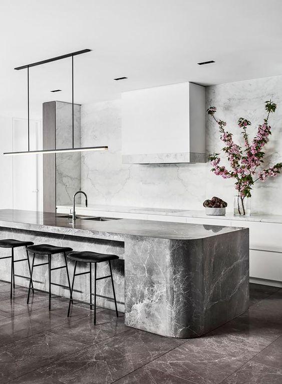 Nhà bếp tối giản với tủ màu trắng kiểu dáng đẹp và máy hút mùi phù hợp, đảo bếp cong bằng đá xám và đèn kiểu dáng đẹp