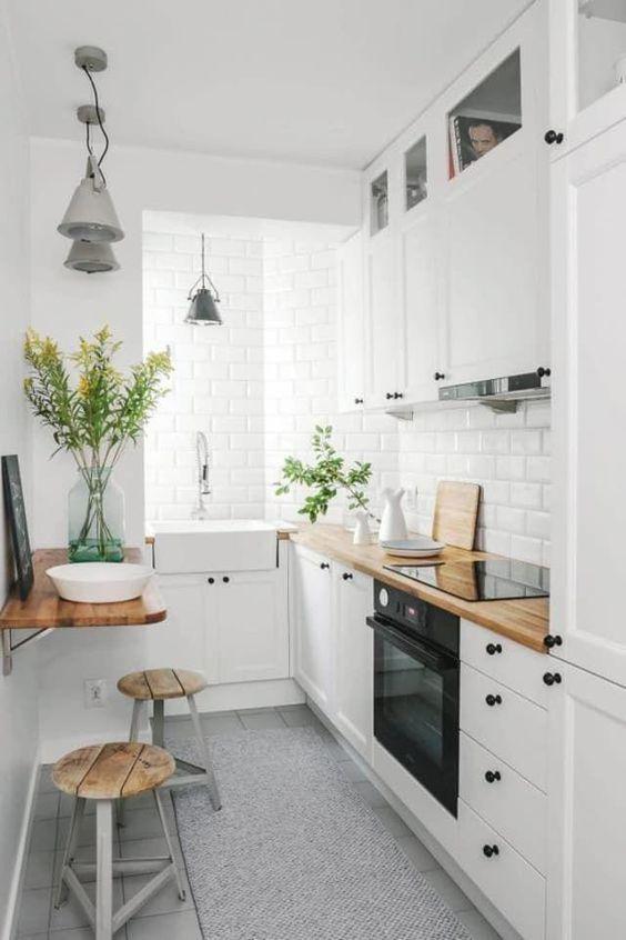 căn bếp nhỏ màu trắng ấm cúng với máy hút mùi kết hợp, mặt bếp bằng butcherblock và các thiết bị tích hợp cùng với khu vực ăn uống nhỏ