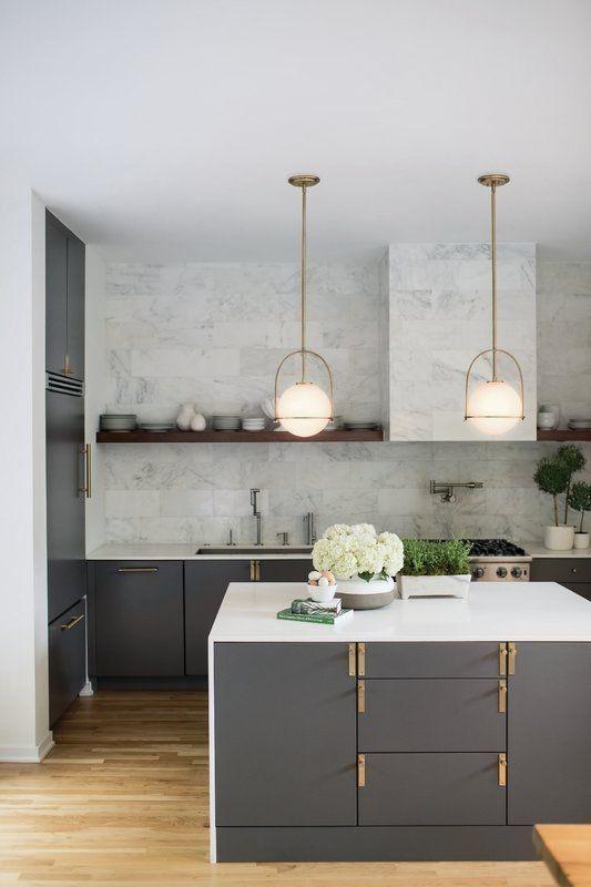 nhà bếp hiện đại sang trọng với tủ màu xám, chạm vàng, mặt bàn màu trắng, gạch đá cẩm thạch trắng trên backsplash và máy hút mùi cộng với đèn mặt dây