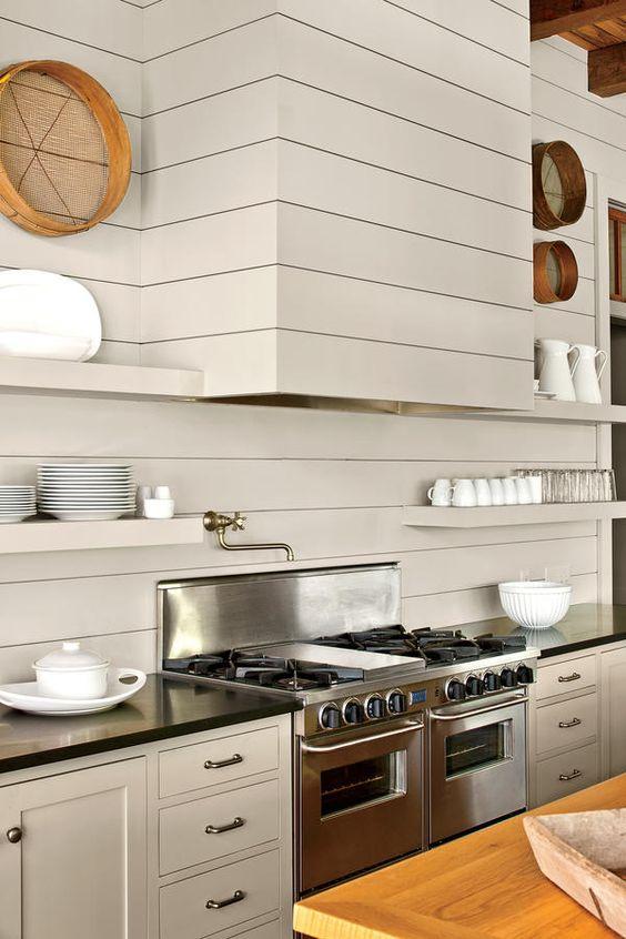 hà bếp hiện đại đầy sáng tạo với bảng màu trắng ngà, mặt bàn màu đen, thiết bị kim loại, máy hút mùi và kệ liền mạch