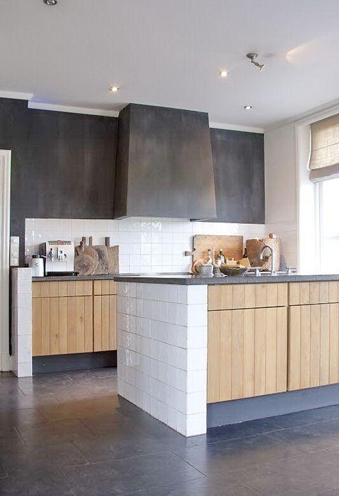 nhà bếp hiện đại với tủ gỗ màu sáng và mặt bàn bê tông, tường bê tông và máy hút mùi tích hợp rất sang trọng