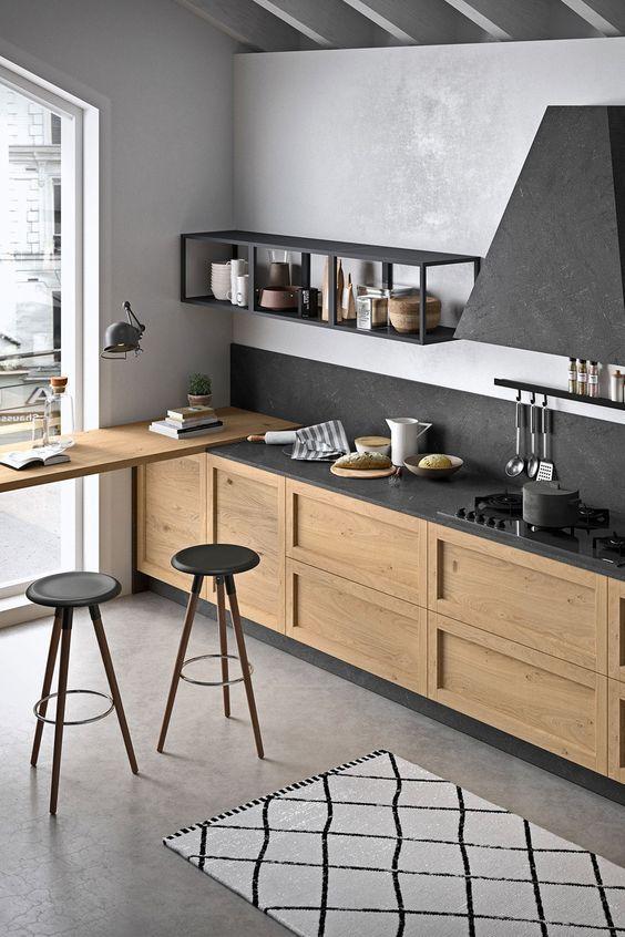 một nhà bếp hiện đại đầy phong cách với tủ màu sáng, mặt bàn bằng đá đen, tấm ốp nền và máy hút mùi