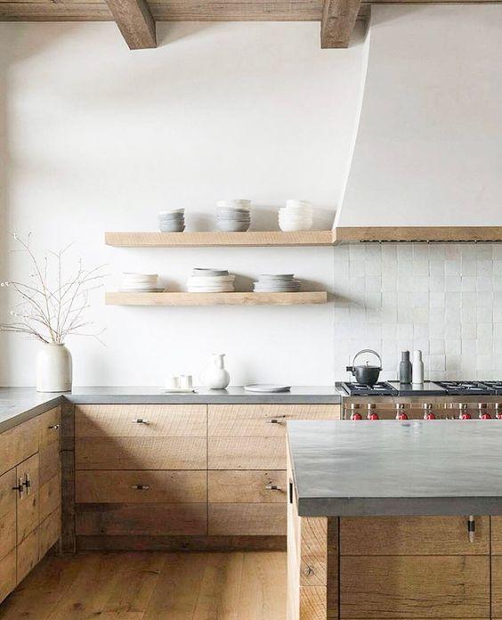 một nhà bếp tối giản thanh bình với tủ thô màu, mặt bàn bê tông, máy hút mùi màu trắng và tấm nền lát gạch trắng trông thật thanh tao