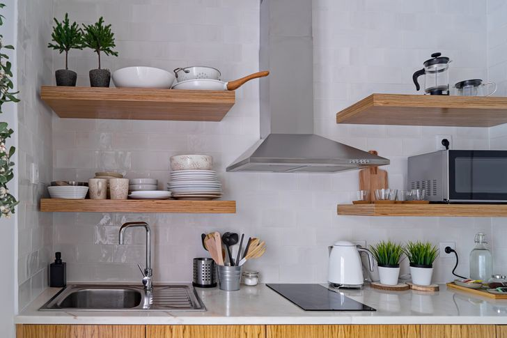 Nhiều người yêu thích xu hướng thiết kế lắp đặt kệ phía trên tủ bếp. Tuy nhiên, bề mặt tích tụ nhiều bụi khiến bạn mất nhiều thời gian vệ sinh đồ dùng khi cần.