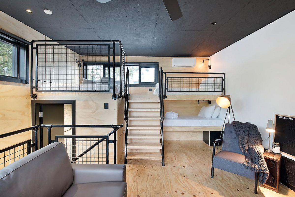 Phòng ngủ công nghiệp hiện đại trên tầng áp mái bằng gỗ và màu đen với lối trang trí thông minh